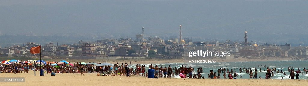 Beach goers crowd a public beach in the southern Lebanese coastal city of Tyre as the Palestinian refugee camp of Rashidieh is seen on the background on June 26, 2016. / AFP / PATRICK BAZ