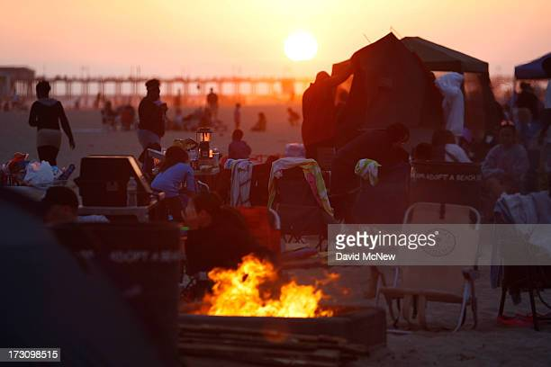 Beach goers gather around traditional beach bonfires at sunset on July 6 2013 in Huntington Beach California Beach fires are a long and stronglyheld...