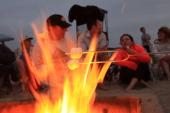 Beach goers roast marshmallows as they gather around traditional beach bonfires on July 6 2013 in Huntington Beach California Beach fires are a long...