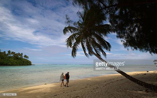 Beach goers walk at Muri beach on the Island of Rarotonga the largest island in the Cook Islands is viewed from the air on August 30 2012 AFP PHOTO /...
