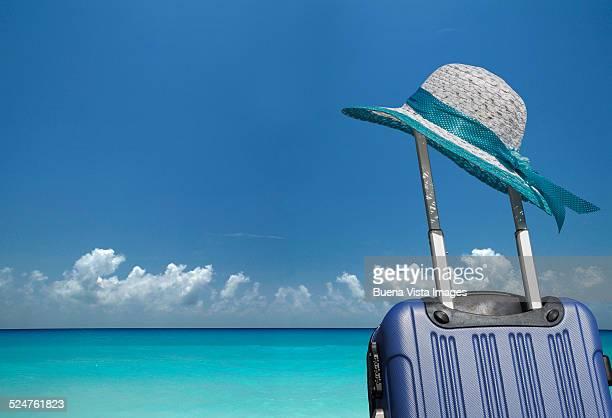 Beach hat on a suitcase on the beach