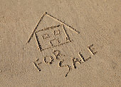 A beach house for sale concept, drawn in the sand at the beach.