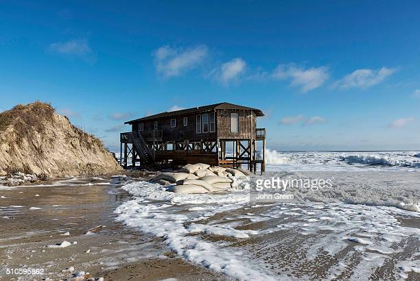Beach house on stilts surrounded by high tide surf
