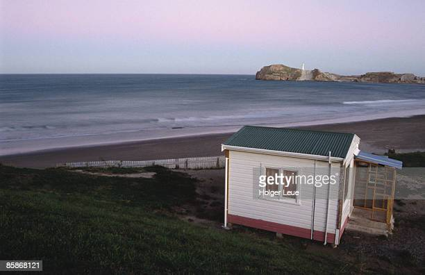 Beach hut and Castlepoint Lighthouse at dusk, Castlepoint.