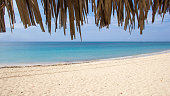 Matanzas, Cuba- March 21, 2016. Photography, shot under a beach hut (or an umbrella made of palm leaves), of a white sandy beach in the Caribbean sea. The sea has different blue tones, from the blue n