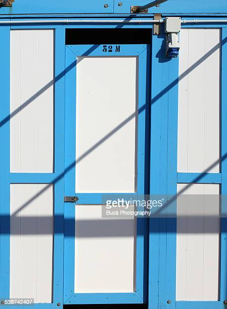 Beach hut painted in bright white and blue colors