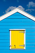 A vertical photograph of a blue and yellow beach hut