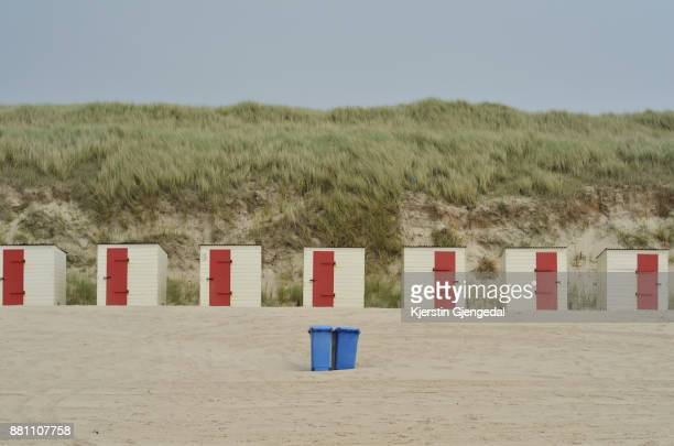 Beach huts and trash bins on a beach, sand dunes in the background.
