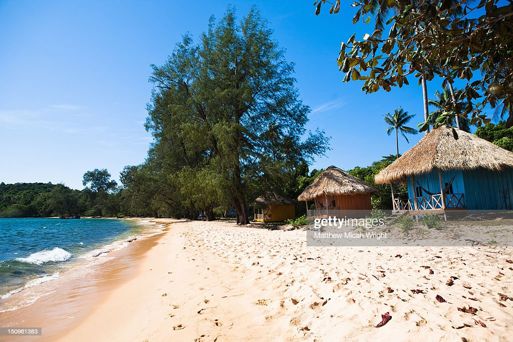 Beach huts line the shore on this small island. : Stock Photo