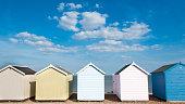Row of six beach Huts at Felixstowe, Suffolk, UK.