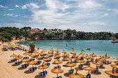 Straw umbrellas on the beach in Porto Cristo on Mallorca, Balearic Islands, Spain
