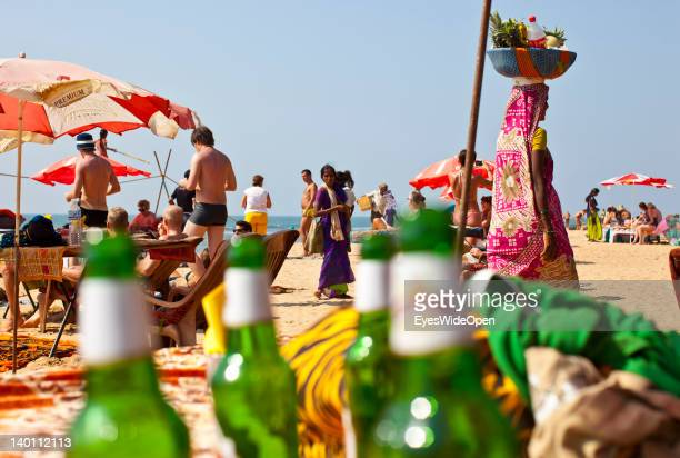 Beach life Empty beer bottles indian female fruit sellers and tourists who are taking a sunbath at the sandy beach of Anjuna on February 1 2012 in...