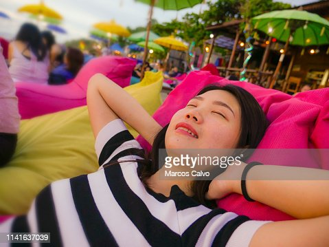 beach lifestyle portrait of young beautiful and happy Asian Chinese woman on her 20s or 30s smiling relaxed and cheerful lying on resort beanbag hammock chilling at tropical bar resort enjoying holidays : Stock Photo