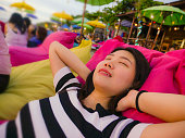 beach lifestyle portrait of young beautiful and happy Asian Chinese woman on her 20s or 30s smiling relaxed and cheerful lying on resort beanbag hammock chilling at tropical bar resort enjoying holida