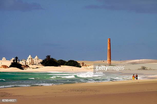 Beach of Praia de Chavez on the west coast of Boa Vista Constructions on the left large chimney and figures of women in swimsuit walking along the...