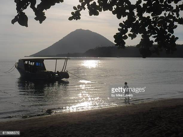 Beach on Bunaken Island with cone of Manado Tua Volcano