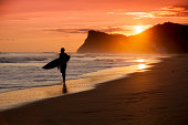 A silhouetted surfer walks down a beach in Nicaragua on sunset during a balmy June afternoon with mountains and ocean in the background. Lots of copy space.