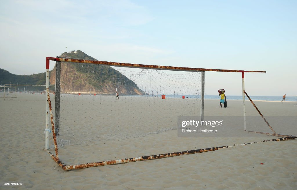 A beach seller carries his stock off the empty Copacabana Beach at 4pm in the afternoon as locals and fans gather around the fanzone to watch the Brazil v Mexico match on June 17, 2014 in Rio de Janeiro, Brazil.