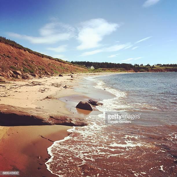 Beach, surf and red sand cliffs on a beach on Prince Edward Island