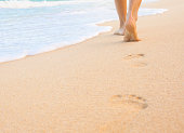 Woman walking on sand beach leaving footprints in the sand. Closeup detail of female feet and golden sand on beach in Hawaii.