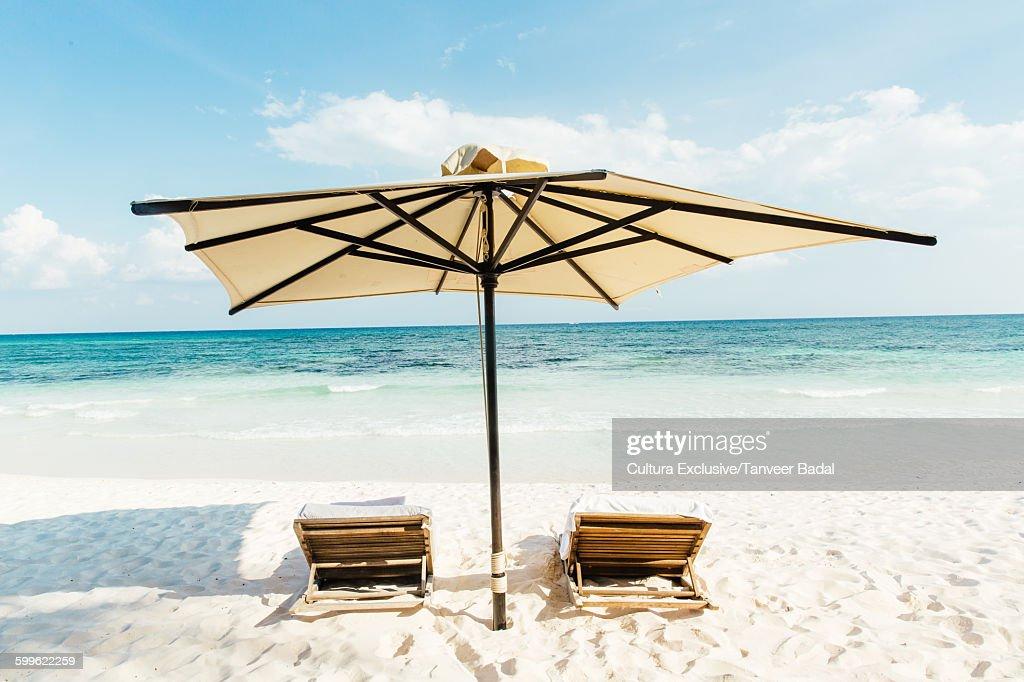 Beach umbrella and sun loungers at beach, Tulum, Riviera Maya, Mexico