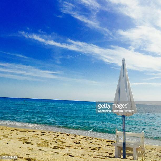 Beach Umbrella On Shore Against Sky