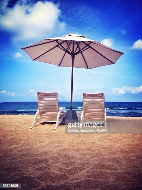 Beach Umbrella With Deck Chairs On Beach Against Sky
