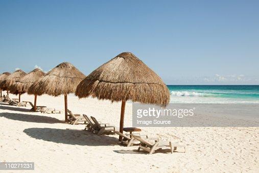 Beach umbrellas and sunloungers on sandy beach : Stock Photo