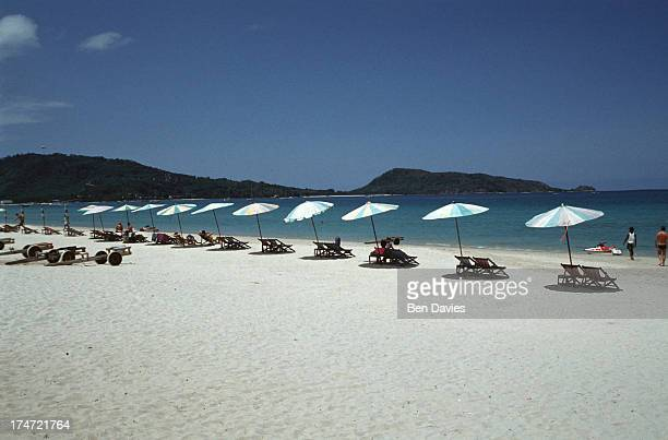 Beach umbrellas spread on the dazzling white sands of Patong Beach on the island of Phuket in Southern Thailand These days Patong has become one of...