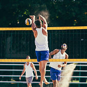 Beach volleyball action - player blocking the ball on the net