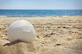 White volleyball sits on top of the sand.