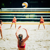 Female team playing beach volleyball, focus on serving player and the ball