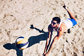 Beach volleyball player jumping for ball