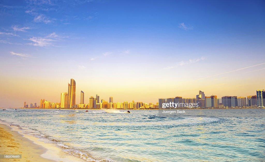 Beach with backdrop of Abu Dhabi skyline at sunset