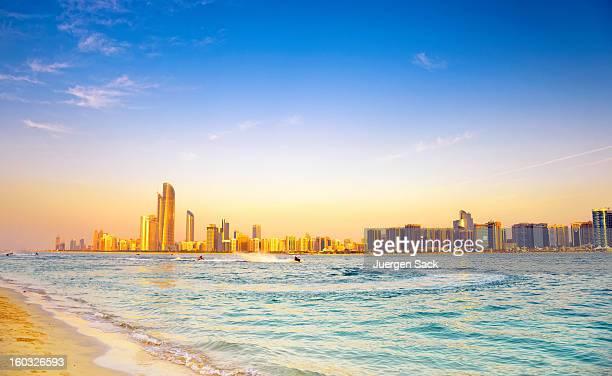 Strand mit Blick auf die skyline von Abu Dhabi bei Sonnenuntergang