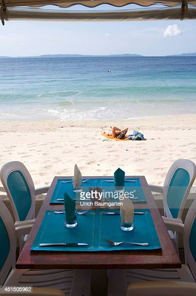 Beach with bathers and laid restaurant table without guests in Cavaliere on June 19 2014 in Cavaliere France