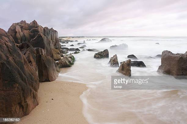 Beach with rocks and blurry waves at sunset