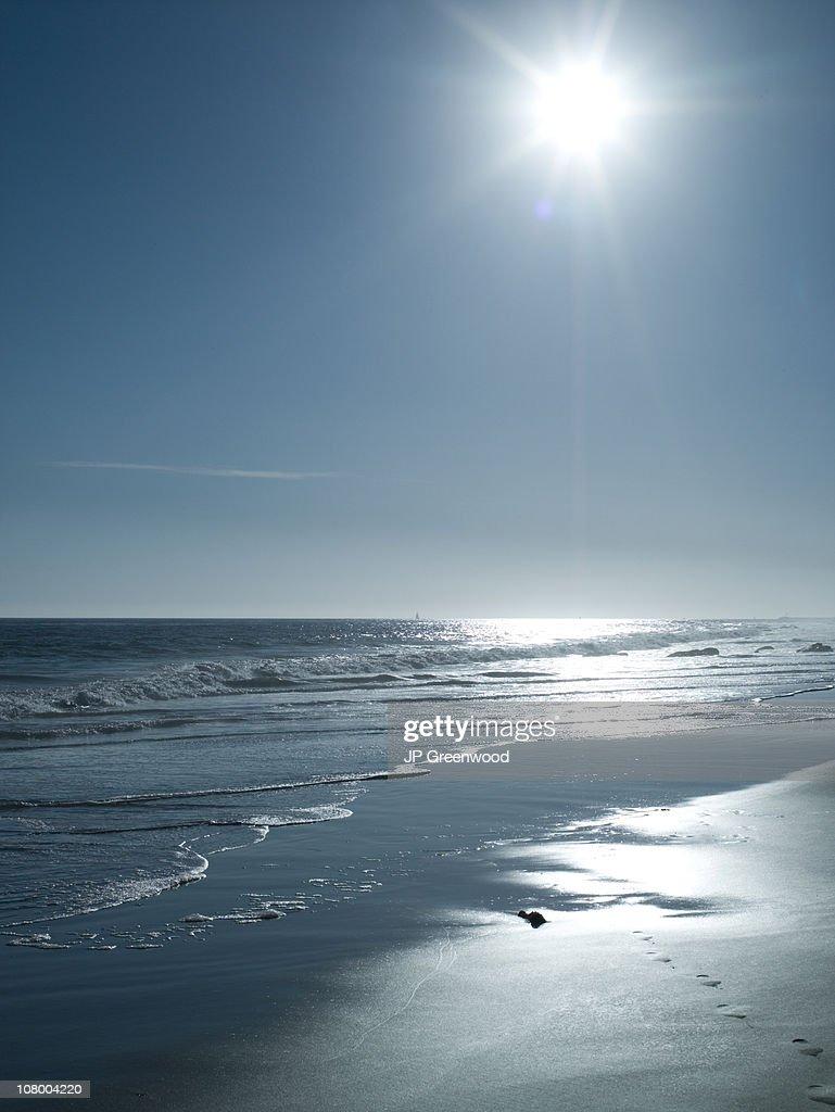 Beach with sun flare : Stock Photo
