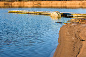 Sandy beach with wooden pier and granite boulder in the water. Location Nattraby, Karlskrona, Sweden.