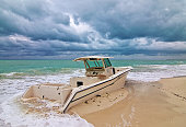 Abandoned Wrecked Beached Fishing Boat under stormy cumulus cloudscape on Isla Blanca peninsula north of Punta Sam and Puerto Juarez on Cancun Mexico Bay