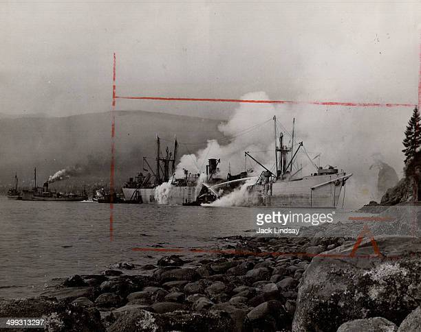 Beached on historic Siwash Rock where she was towed after six explosions ripped her hull and shook downtown Vancouver yesterday noon the freighter...