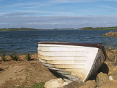 A rowing boat beached on a lakeside