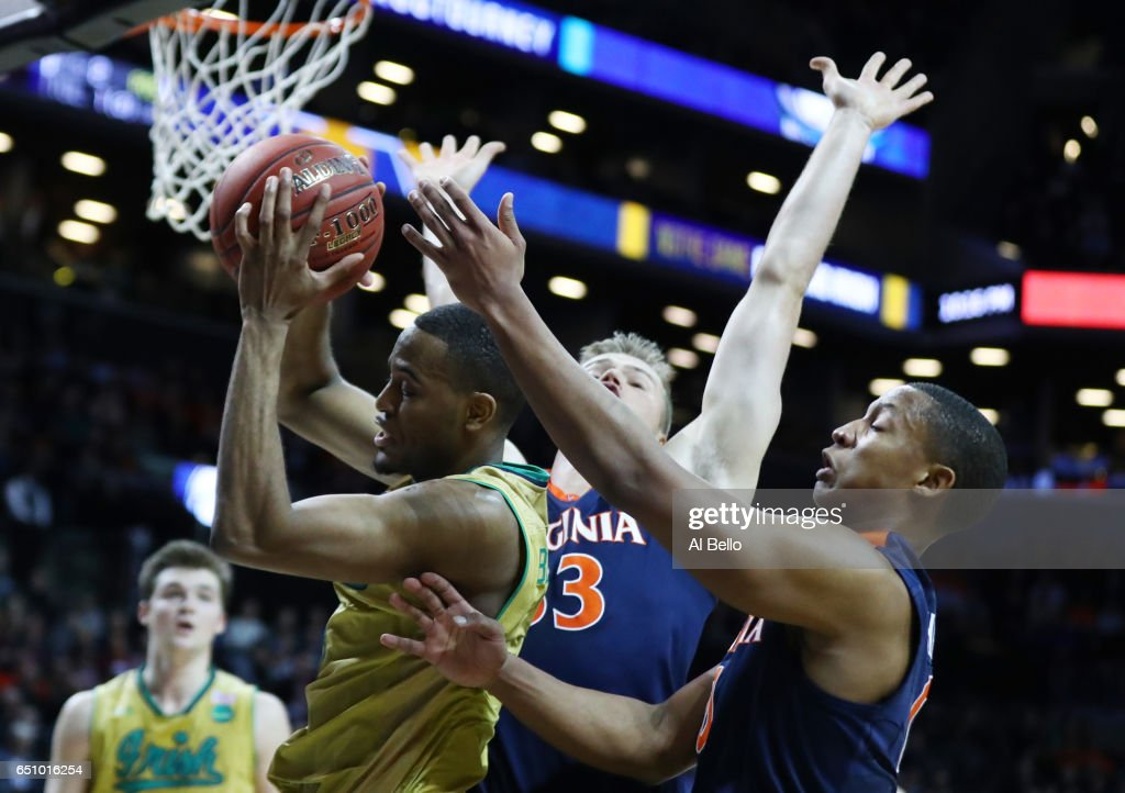 V.J. Beachem #3 of the Notre Dame Fighting Irish battles for the ball with Devon Hall #0 of the Virginia Cavaliers during the Quarterfinals of the ACC Basketball Tournament at the Barclays Center on March 9, 2017 in New York City.