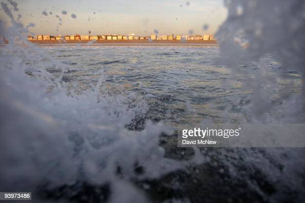 Beachfront homes are seen beyond breaking waves on December 4 2009 on the flat sands of Sunset Beach California A report released this week called...