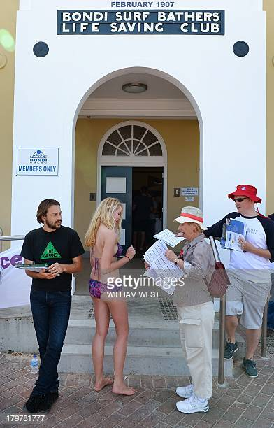 A beachgoer is given information on how to vote outside a polling booth at Sydney's Bondi Beach on September 7 in Australia's general election Polls...