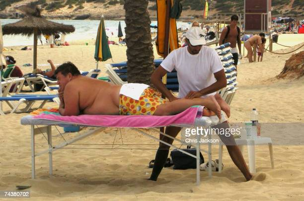 A beachgoer recieves a massage on Playa D'En Bossa on June 2nd 2007 in Ibiza Spain Ibiza remains one of the world's top holiday destinations for...