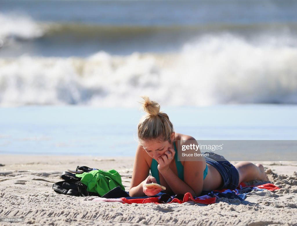A beachgoer relaxes as four to six foot swells hit the beach off the Atlantic Ocean on August 28, 2014 in Long Beach, New York. Hurricane Cristobal is churning up larger than normal waves along the eastern coast of the United States.