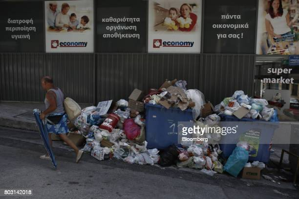 A beachgoer walks past pile of uncollected garbage on a sidewalk during a refuse collection strike by municipal workers in Athens Greece on Wednesday...