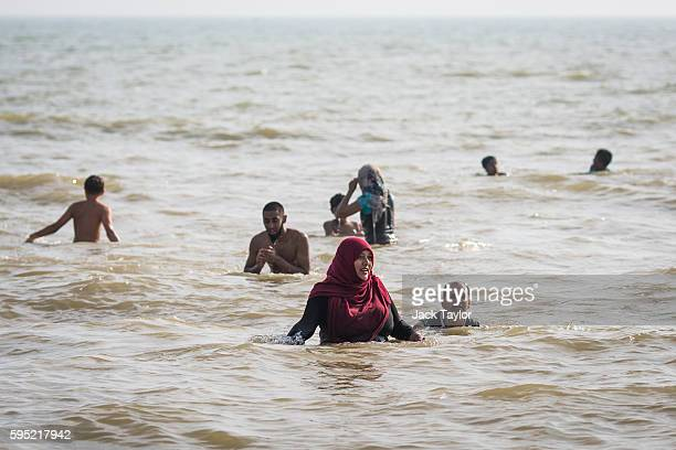 Beachgoers play in the sea on Camber Sands on August 25 2016 in Rye England Five men were found dead after being pulled from the sea on the hottest...