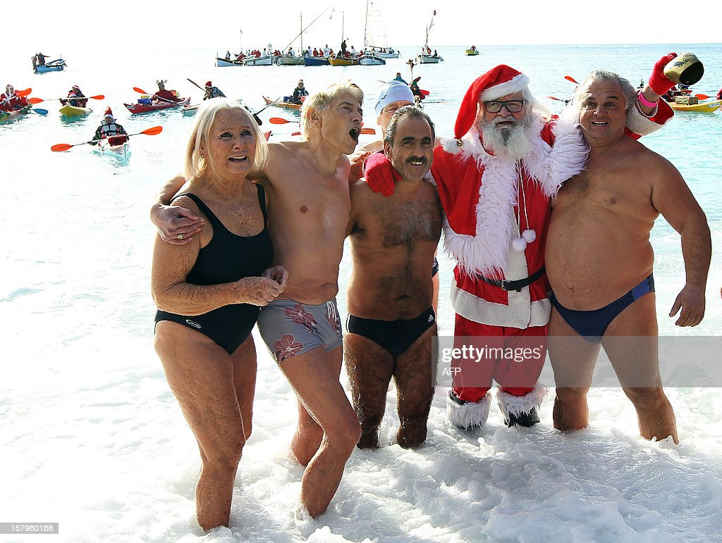 Beachgoers pose with a man wearing a Santa Claus costume as they stand in the Mediterranean Sea on December 8, 2012 in Nice, southern France.